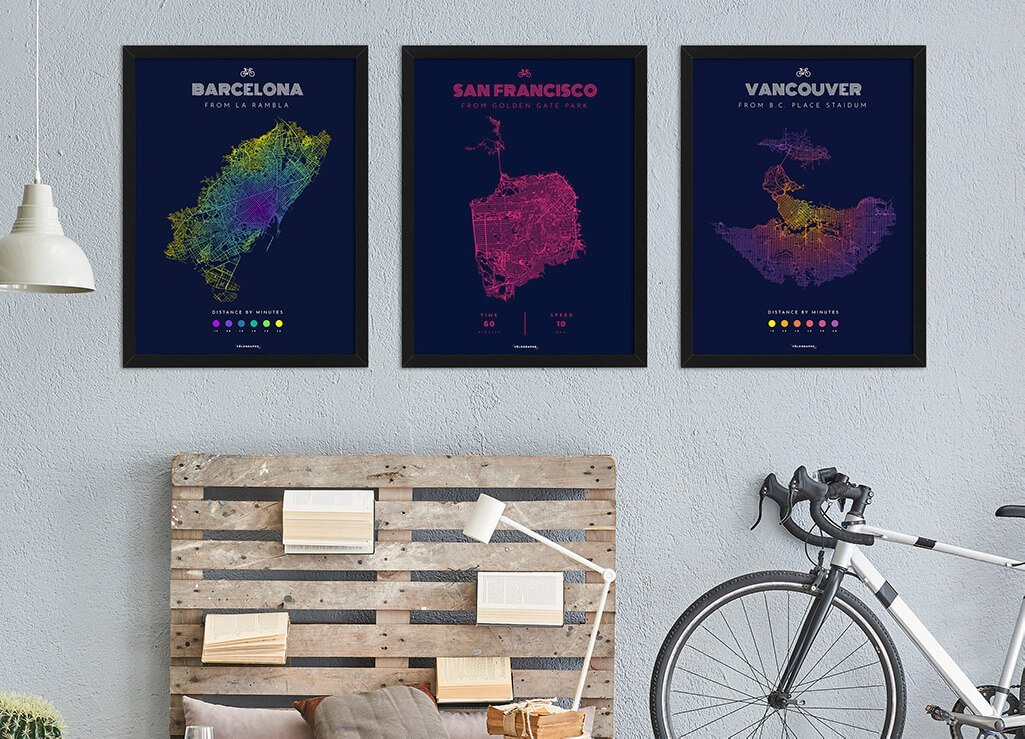 Three posters, made by Vélographs, hanging on the wall, showing the reachable area by bike of three different cities.